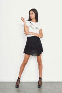 Modella con minigonna a balze nera e t-shirt bianca